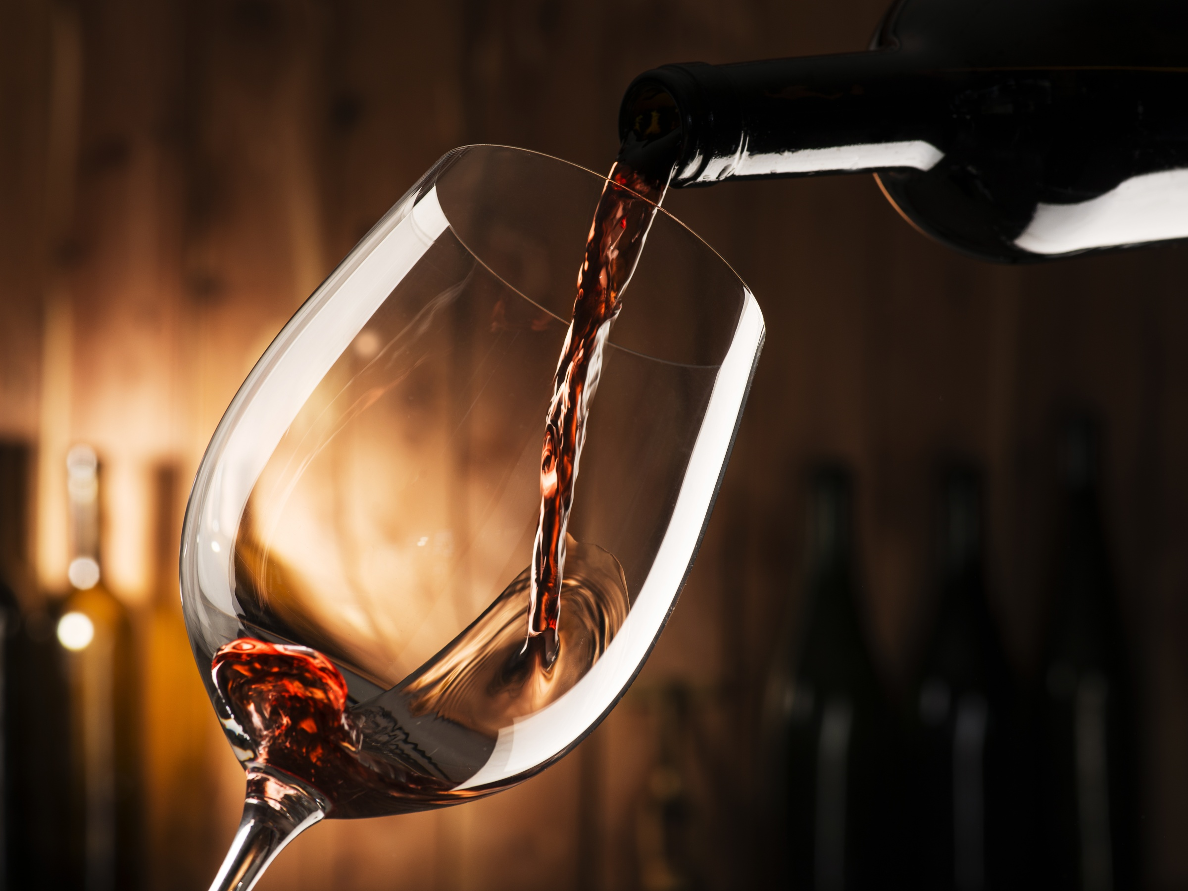 glass with red wine on wooden background
