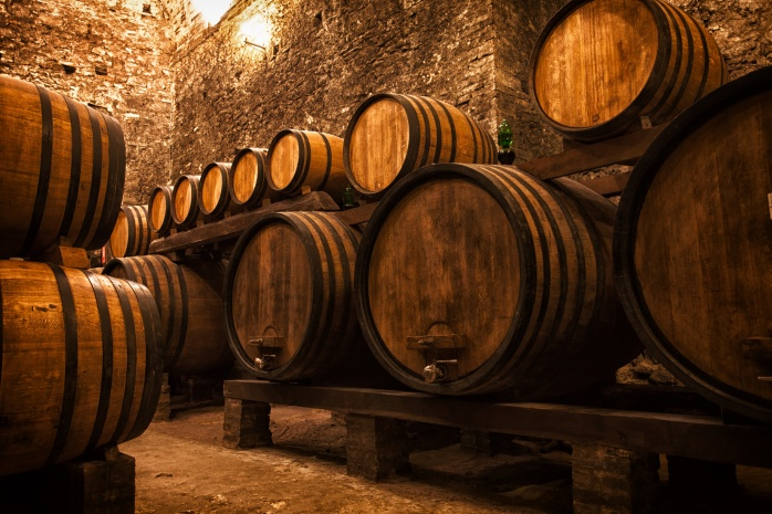 Old winery cellar with barrels for storing wine.